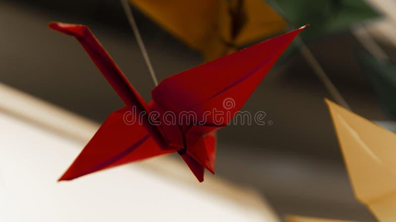 Rode de slingerooievaar van de origamivogel op lichte achtergrond stock fotografie