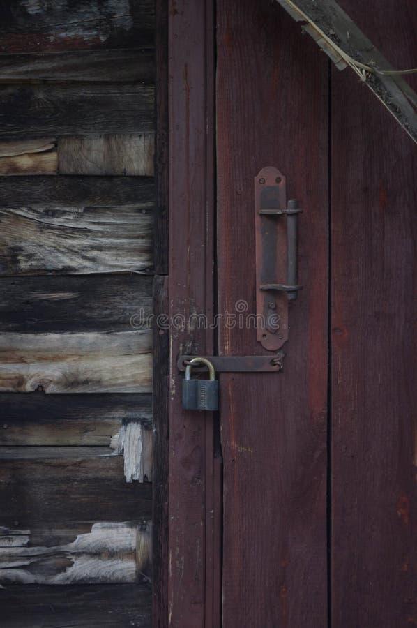 Rode deur en houten muur oud hangslot op de oude deur stock foto's