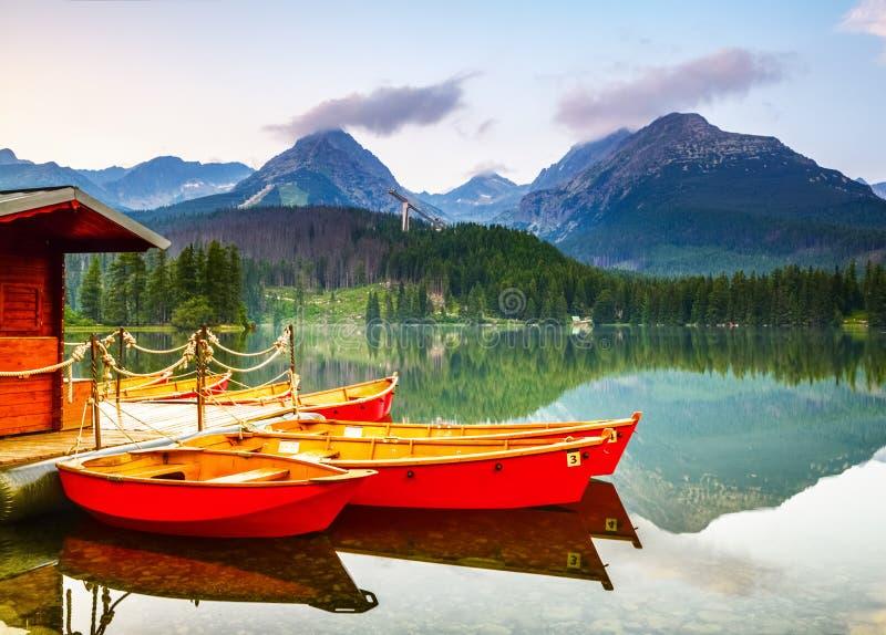 Rode die boten bij blokhuis op een meer worden vastgelegd royalty-vrije stock afbeeldingen