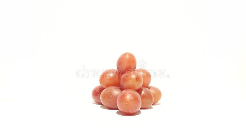 Rode die Druiven in een Piramide op Witte Achtergrond worden gestapeld stock afbeelding