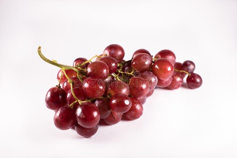 Rode die druiven met stelen op witte achtergrond worden geïsoleerd royalty-vrije stock foto's