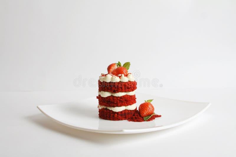 Rode die fluweelcake op een plaat op wit wordt ge?soleerd stock afbeelding