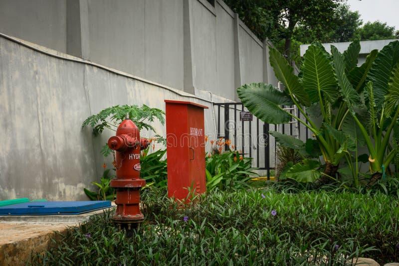 Rode die hydrantdoos en pomp in binnenplaats het omringen door hoge muurfoto in Djakarta Indonesië wordt genomen royalty-vrije stock afbeeldingen