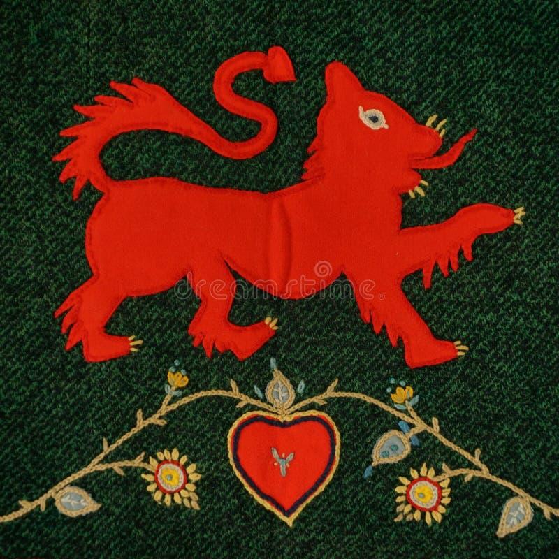 Rode die leeuwpoot op geslepen deken van stoffenresten wordt opgeheven stock afbeeldingen