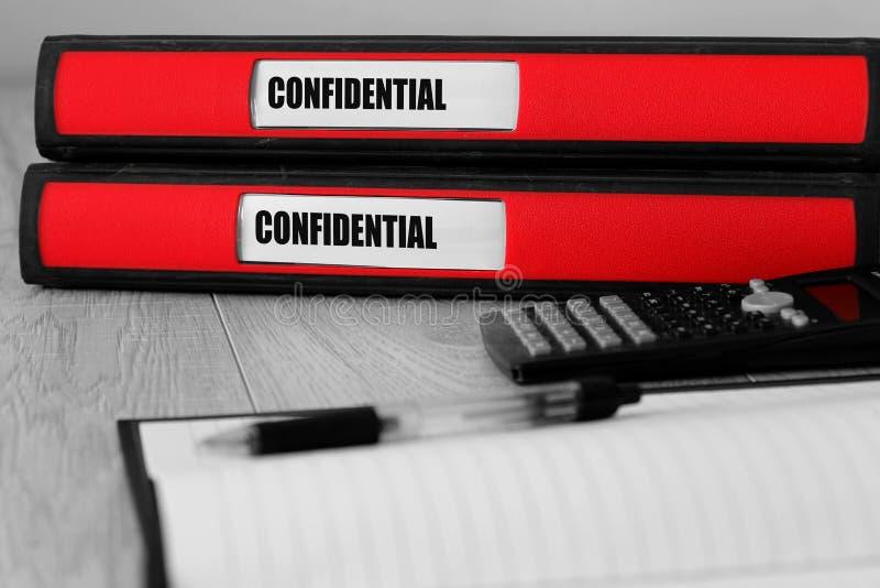 Rode die omslagen met vertrouwelijk op het etiket op een bureau worden geschreven royalty-vrije stock afbeeldingen