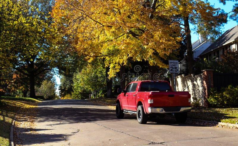 Rode die pick-up op bladbuurtstraat wordt geparkeerd in de Herfst royalty-vrije stock foto's