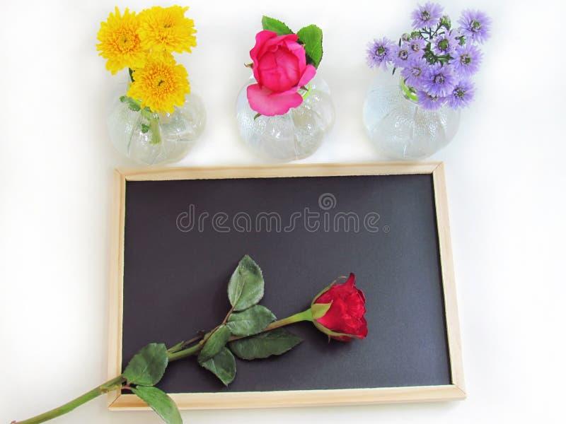 Rode die rozen op het bord en de gele chrysant worden geplaatst, roze rozen en de purpere bloem van Margaret in flessenvazen royalty-vrije stock afbeeldingen