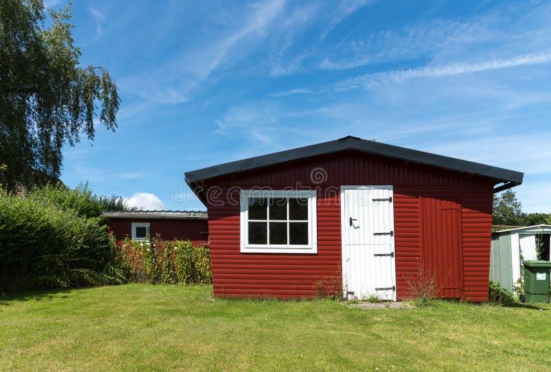 Rode die tuin met witte deur op een zonnige dag wordt afgeworpen stock foto