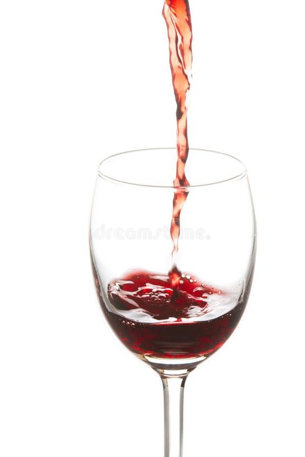 Rode die wijn in een wijnglas wordt gegoten royalty-vrije stock afbeelding