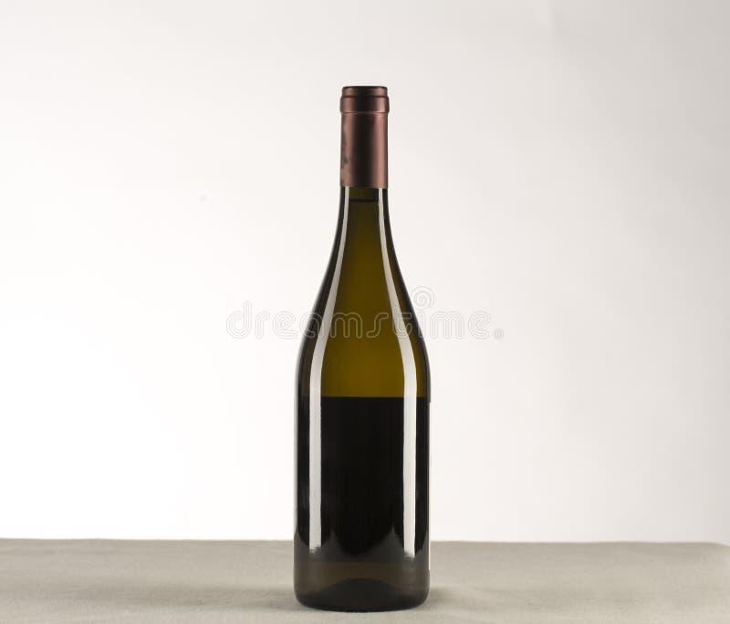 Rode die wijn en een fles over witte achtergrond wordt geïsoleerd stock fotografie