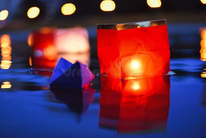 Rode document lantaarns die in donker water bij nacht drijven stock afbeelding