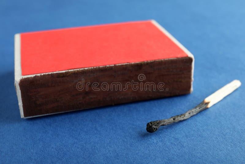 Rode doos en gebrande gelijke op kleurenachtergrond stock afbeeldingen