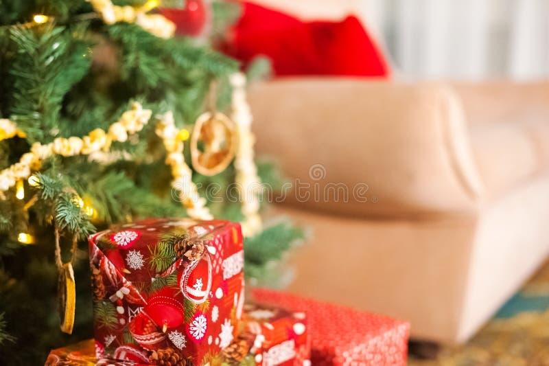 Rode doos met een gift onder een Kerstboom op een achtergrond van een beige bank met rode hoofdkussens tegen de achtergrond van b stock afbeelding