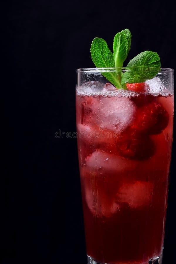 Rode drank met ijs, frambozen en munt in een lang glas stock afbeelding
