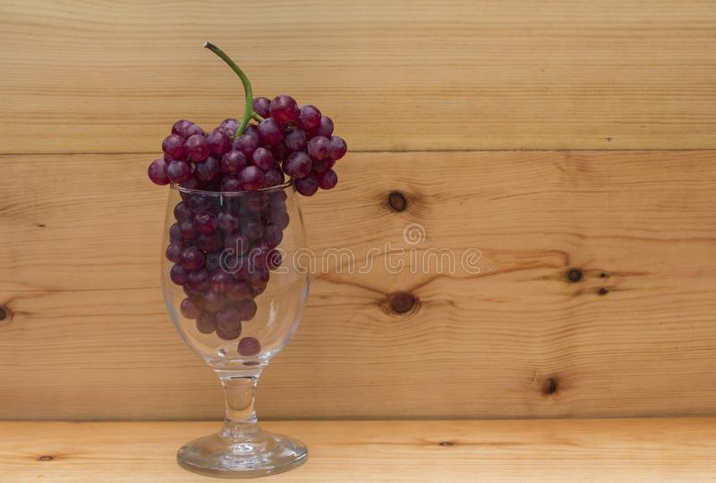Rode druiven in een glas op een houten achtergrond royalty-vrije stock foto's
