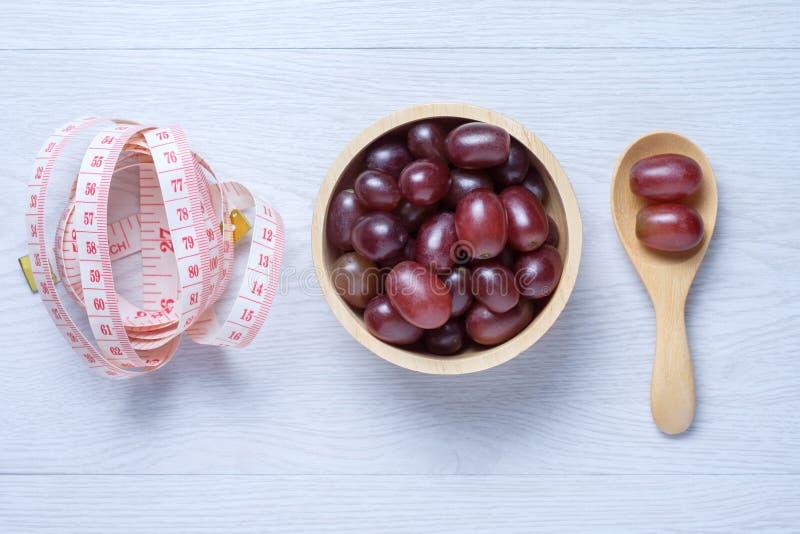 Rode druiven in houten kom en lepel stock foto's