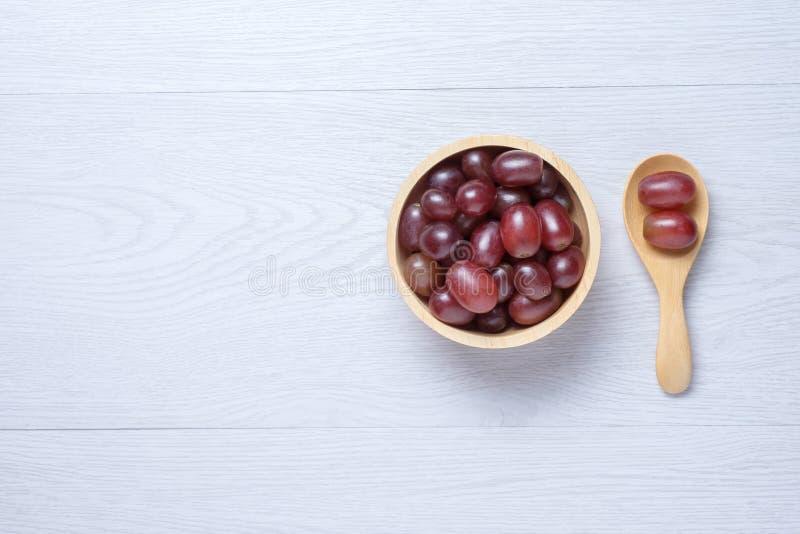 Rode druiven in houten kom en lepel royalty-vrije stock fotografie