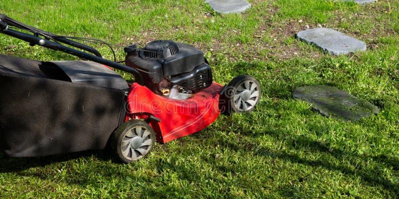 Rode duwgrasmaaimachine in de Lentezomer in gras groene tuin stock afbeelding