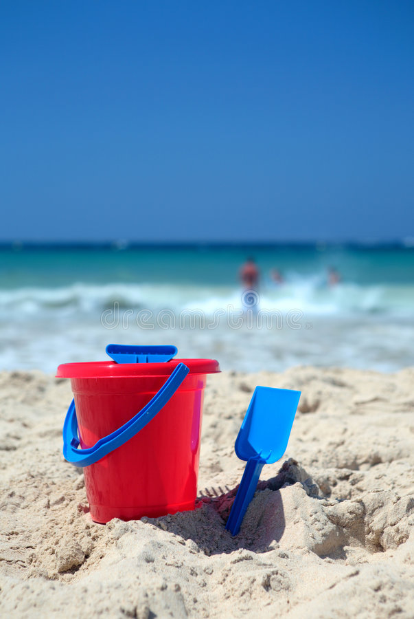 Rode emmer en blauwe spade op zonnig zandig strand stock fotografie