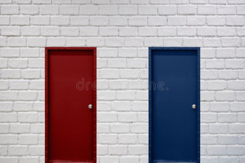 Rode en blauwe deuren op witte bakstenen muur voor economisch besluitmak royalty-vrije stock fotografie