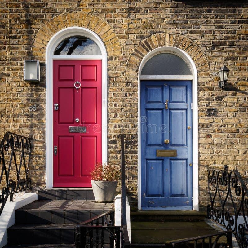 Rode en Blauwe deuren van een terras Georgisch huis in Londen het UK stock foto