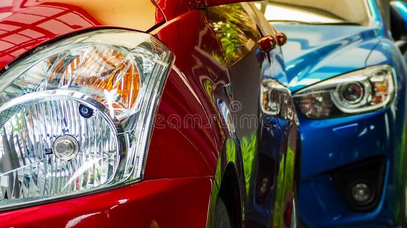 Rode en blauwe die SUV-auto op concreet parkeerterrein van het hotel, het huis, of de flat wordt geparkeerd De automobielindustri royalty-vrije stock foto's