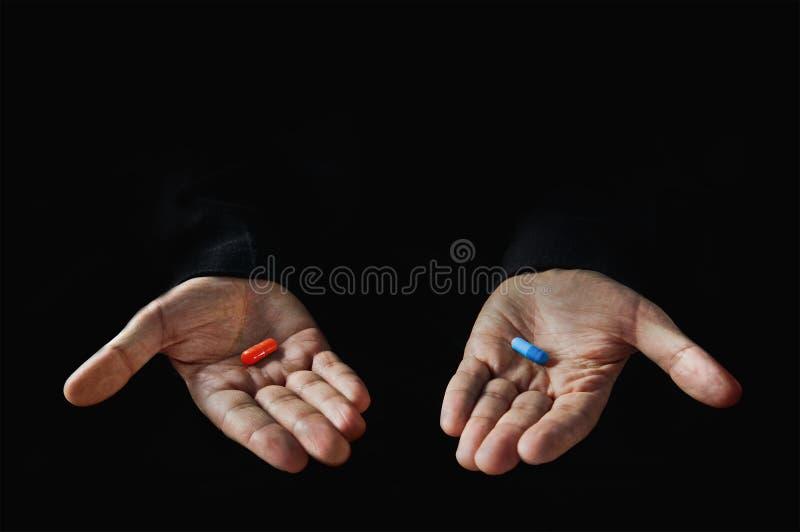 Rode en blauwe pillen op geïsoleerde hand royalty-vrije stock fotografie