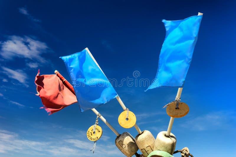 Rode en blauwe vlaggen op vlottersvisnetten tegen de hemel stock foto