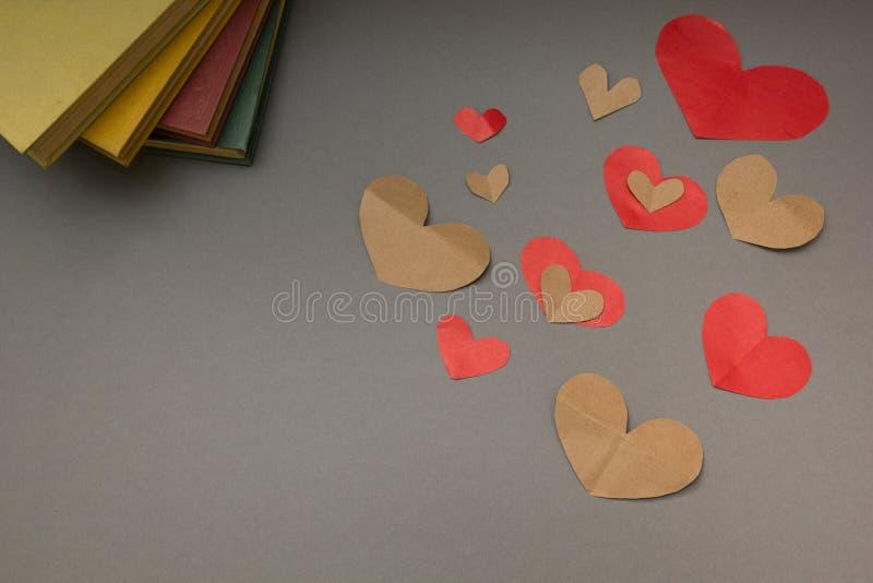 Rode en bruine harten en het boek op een grijze achtergrond stock fotografie