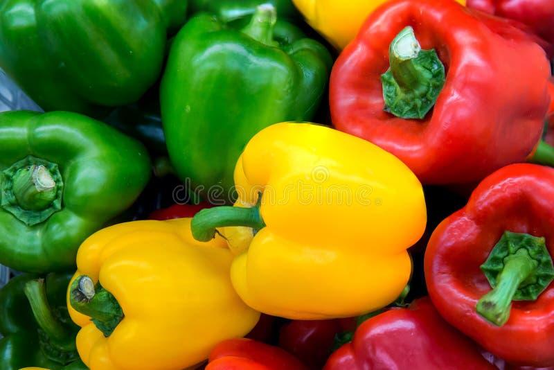Rode en gele en Groene paprika's Stapel Drie paprika's op een houten achtergrond, Kokende plantaardige salade stock fotografie
