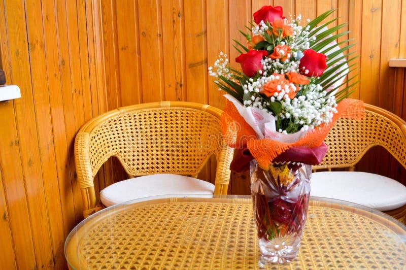 Rode en gele rozen in een boeket met gestrooide witte bloemen op een tabl stock foto