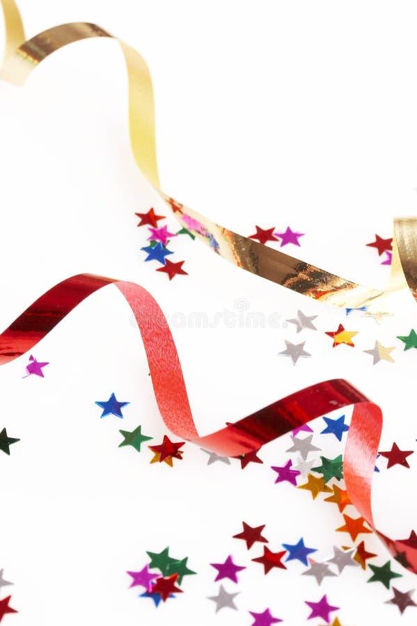 Rode en gouden kleurrijke linten en kleine confettien stock afbeelding