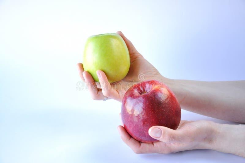 Rode en groene appel in handen op witte achtergrond royalty-vrije stock afbeelding
