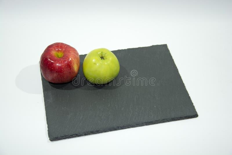 Rode en groene appelen die op een dienend rek van lei liggen royalty-vrije stock fotografie
