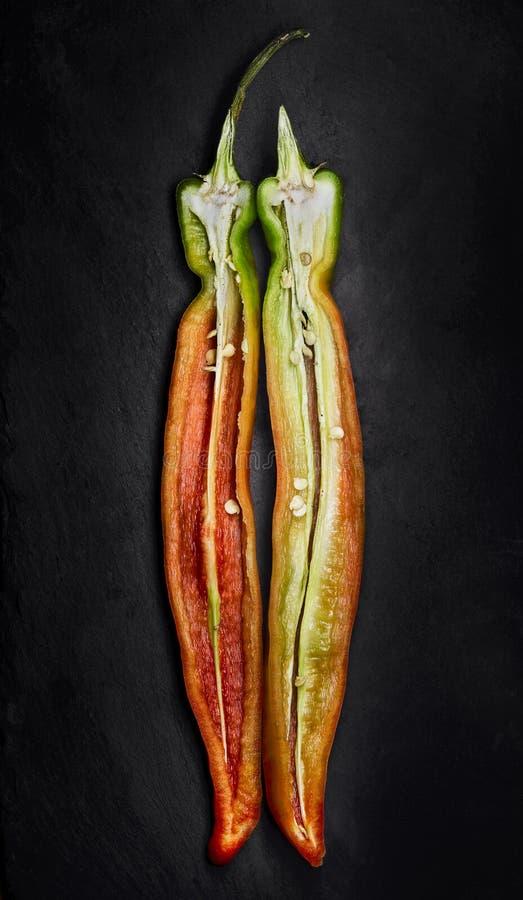 Rode en groene die Spaanse peperspeper in de lengte over een zwarte lei wordt gesneden royalty-vrije stock afbeelding