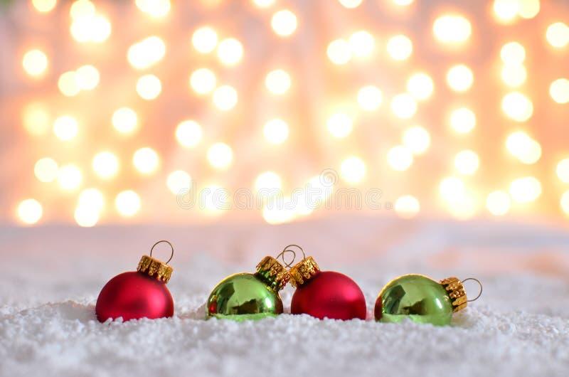 Rode en groene ornamenten in sneeuw met bokehachtergrond stock foto's