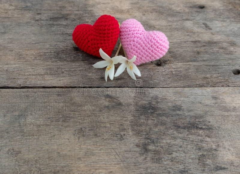 Rode en roze nitting harten met bloemen op houten lijst stock afbeeldingen