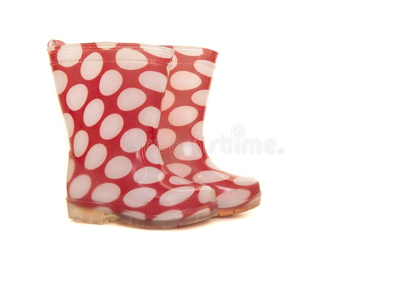 Rode en witte die polka rainboots voor jonge geitjes wordt gestippeld op whit worden geïsoleerd stock afbeelding