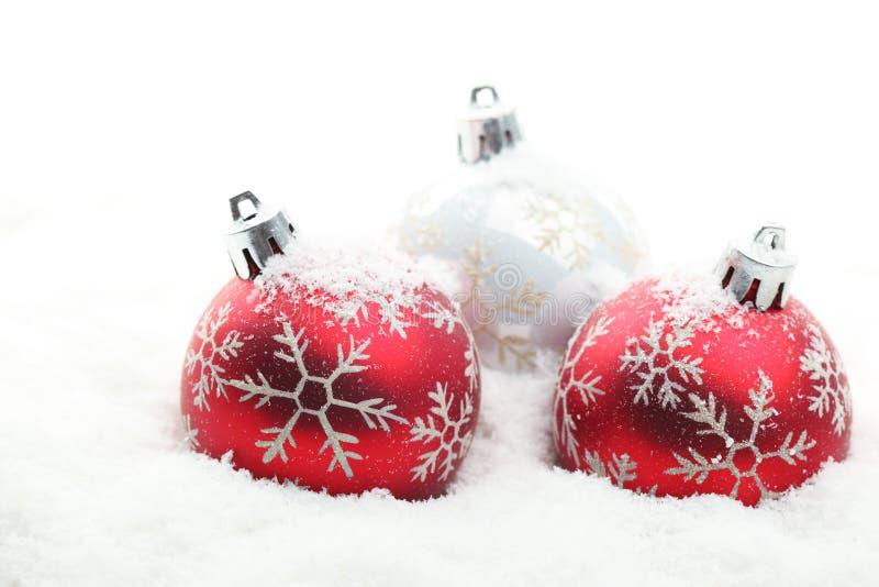 Rode en witte Kerstmisballen in sneeuwvlokken stock foto