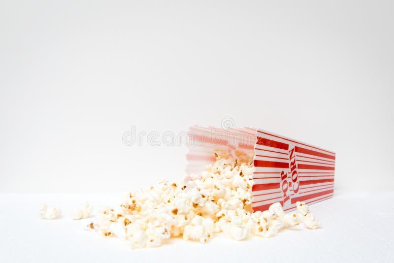Rode en witte popcorncontainer met gemorste popcorn op grond royalty-vrije stock foto