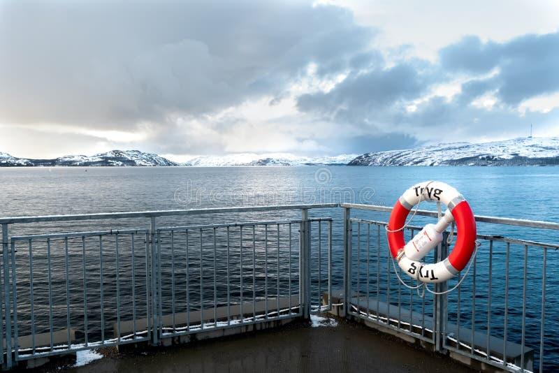 Rode en witte reddingsboei op een hindernis op de meertros tegen de achtergrond van het noordelijke overzees stock fotografie