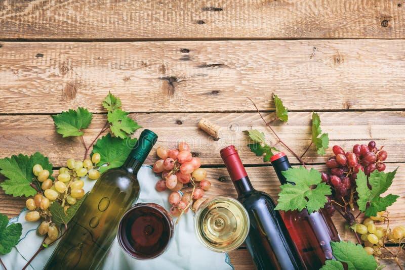 Rode en witte wijnglazen en flessen op houten achtergrond, exemplaarruimte Verse druiven en druivenbladeren als decoratie stock fotografie