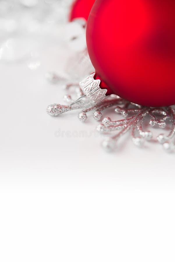 Rode en zilveren Kerstmisornamenten op heldere vakantieachtergrond royalty-vrije stock afbeelding