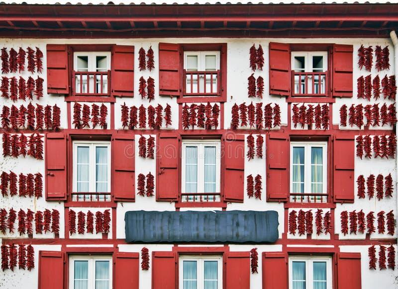 Rode Espelette-peper die in de muur van Baskisch huis drogen stock afbeeldingen