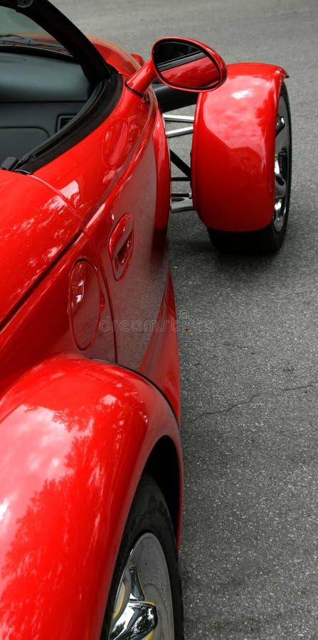 Rode exotische sportwagen met mening in zijspiegel stock foto's