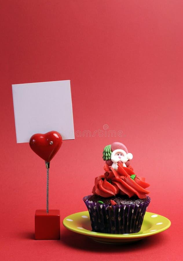 Rode feestelijke cupcake van Santa Christmas met het lege teken van de plaatskaart. Verticaal. stock foto's