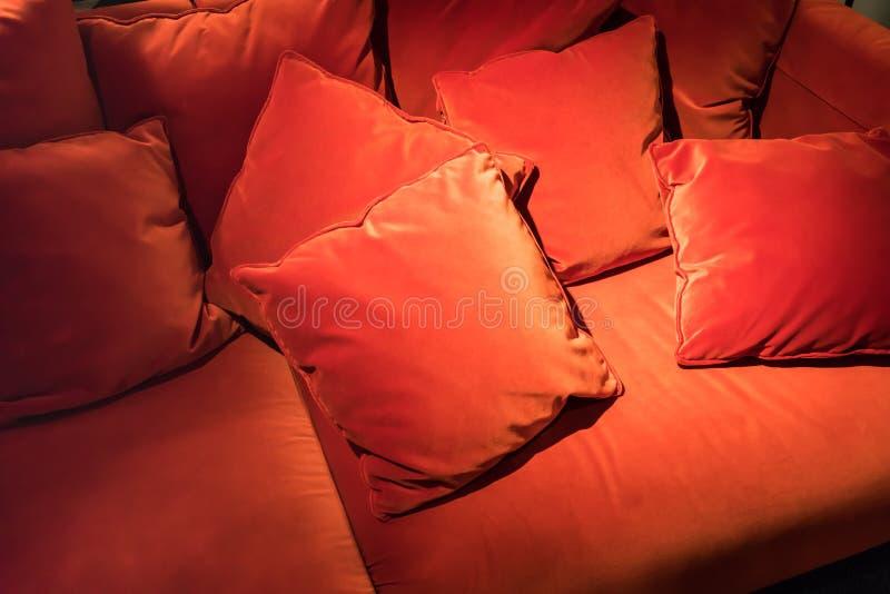 Rode fluweel vierkante hoofdkussens op rode fluweelbank voor samenvatting backgr royalty-vrije stock afbeeldingen