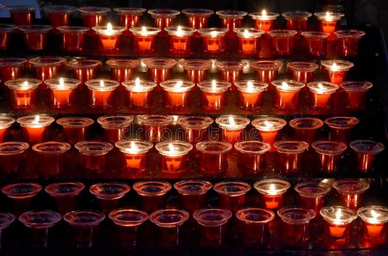Rode gebedkaarsen in een kerk royalty-vrije stock foto