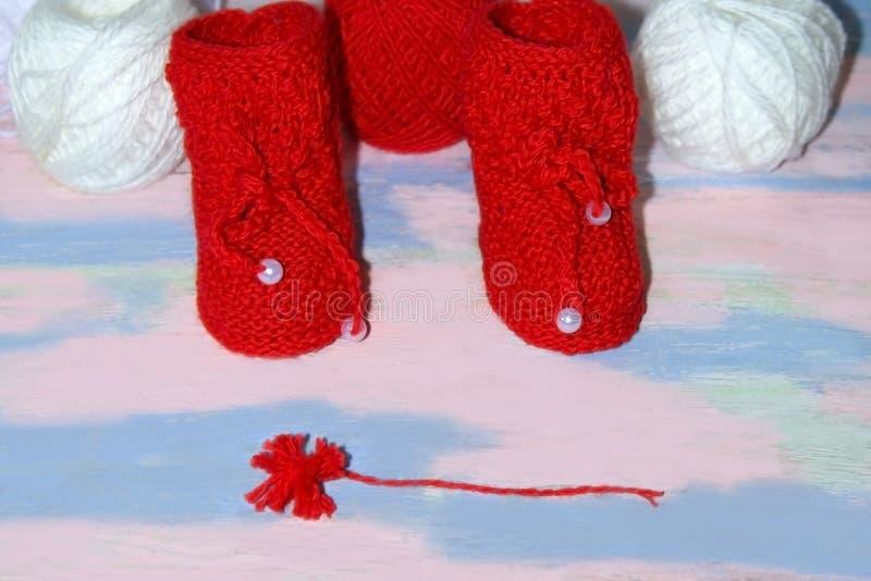 Rode gebreide babybuiten, een rode bal van wolgaren voor het breien en een rode pompon van garen op een roze - blauwe achtergrond stock afbeelding
