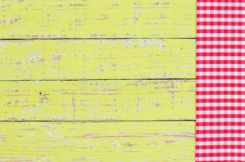 Rode gecontroleerde tafelkleedgrens op oude rustieke groene houten lijstachtergrond stock foto